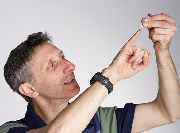 Nick Goldman betrachtet ein Proberöhrchen, indem sich synthetische DNA befindet.